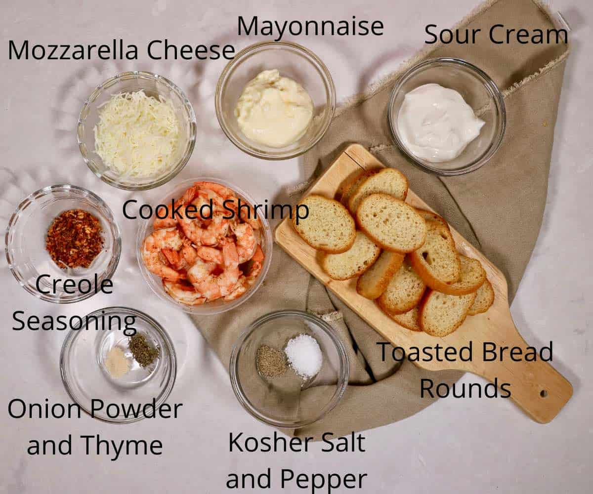 Cooked shrimp, toast, cheese and mayonnaise on a counter.