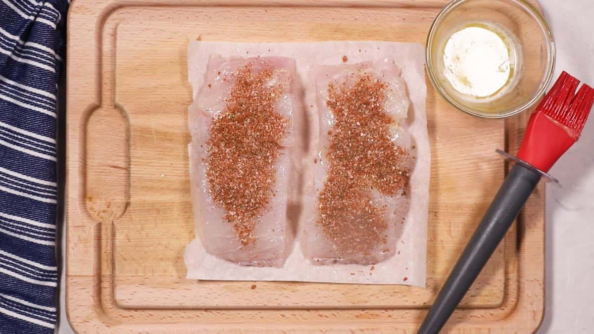 Two fish fillets topped with blackening seasoning.