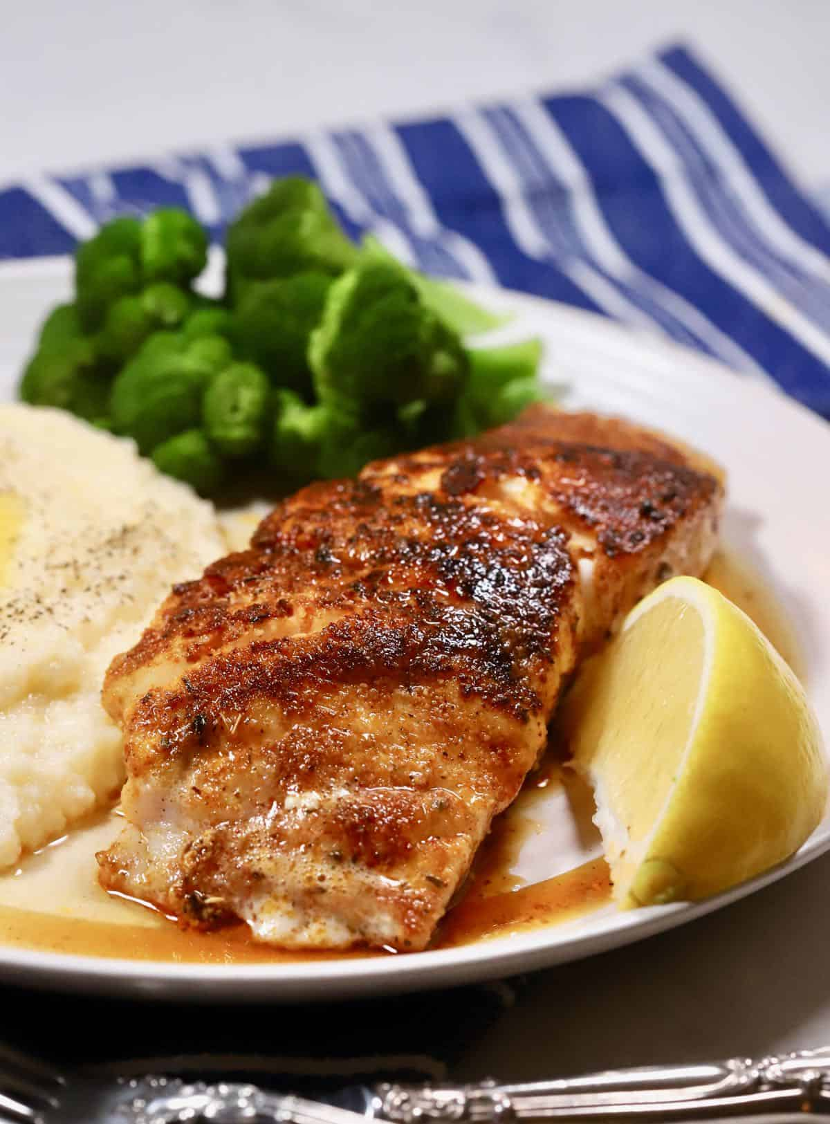 Blackened grouper on a white plate with grits.
