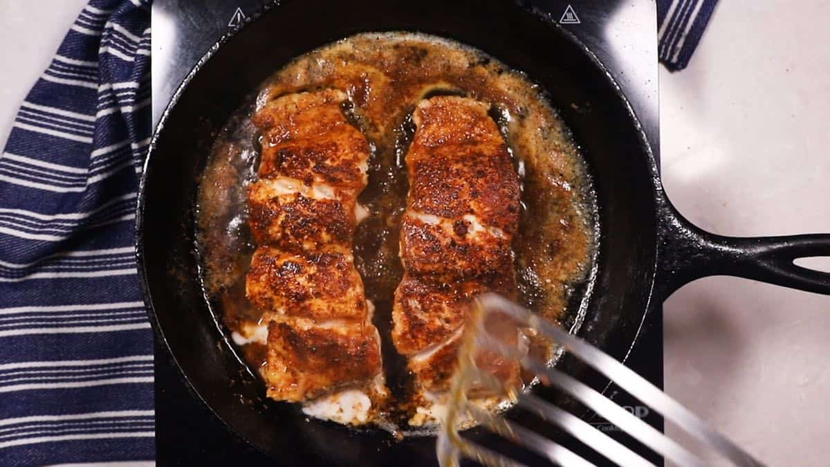 Two grouper fillets cooking in a cast-iron skillet.