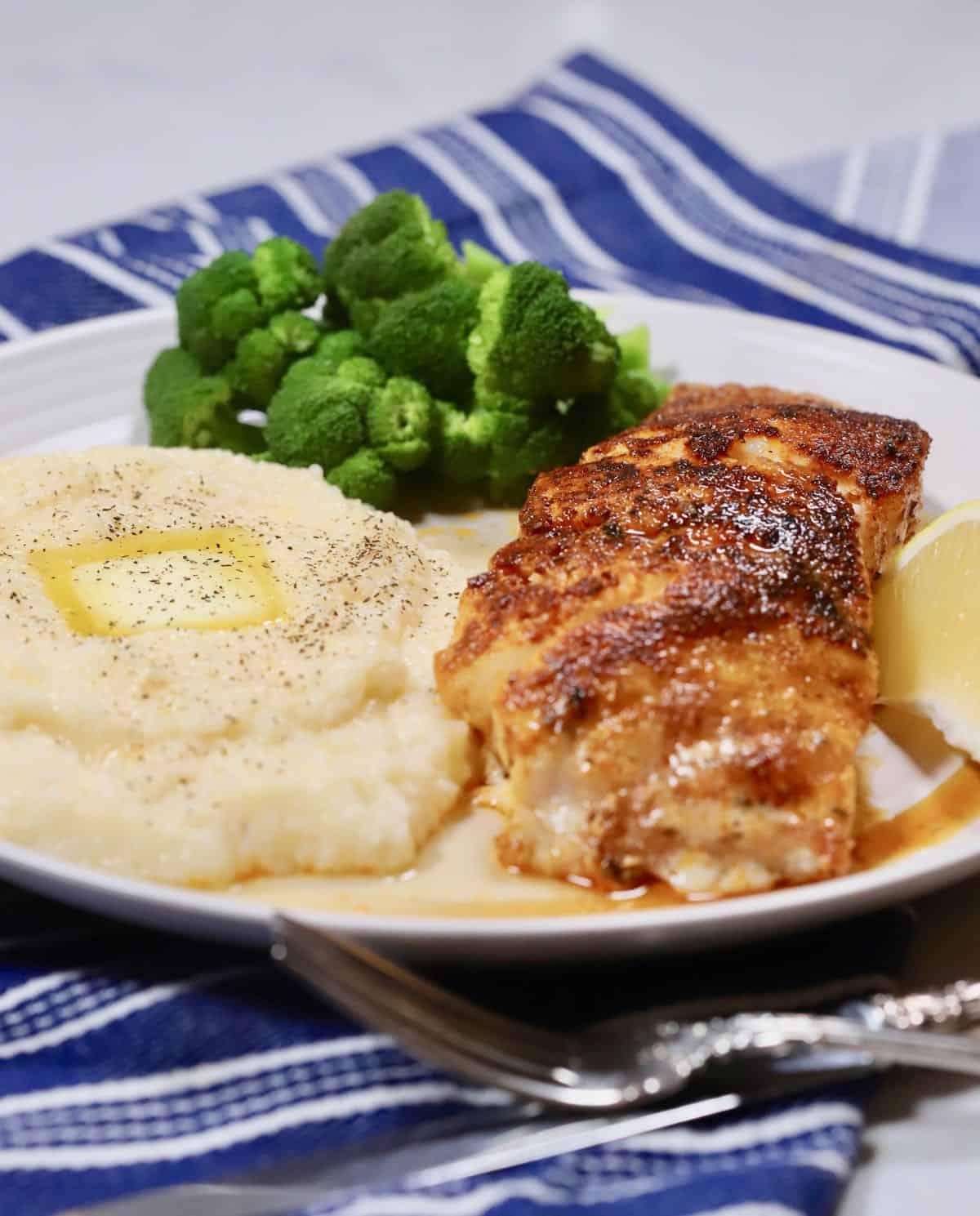 Blackened grouper fillet with grits and broccoli on a plate.