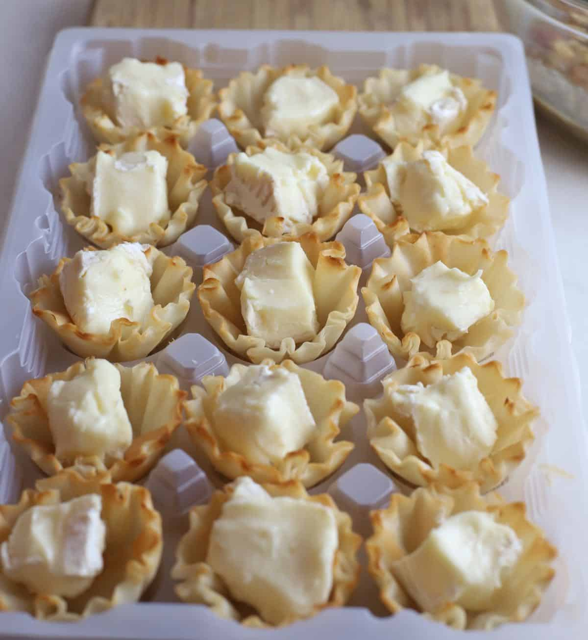 Cubes of brie cheese in phyllo shells on a baking sheet.