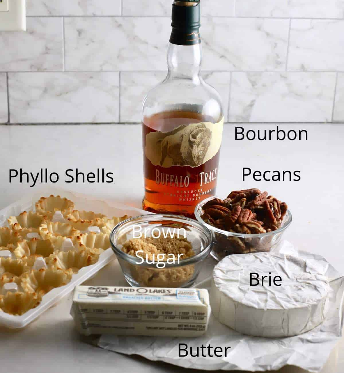 Ingredients to make brie bites including bourbon, phyllo shells, and brie cheese.