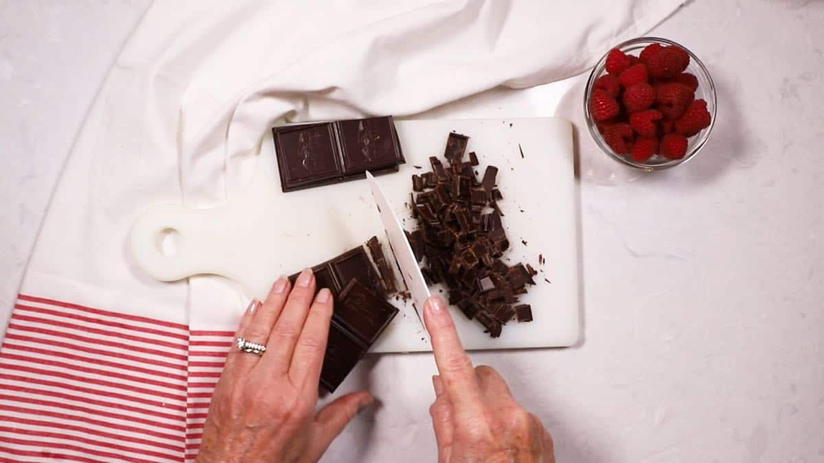 Cutting up baking chocolate on a cutting board.