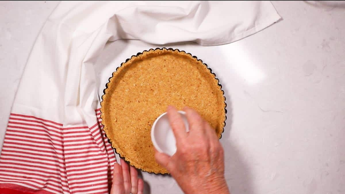 Using a flat-bottomed measuring cup to pack down a cookie crumb tart crust.