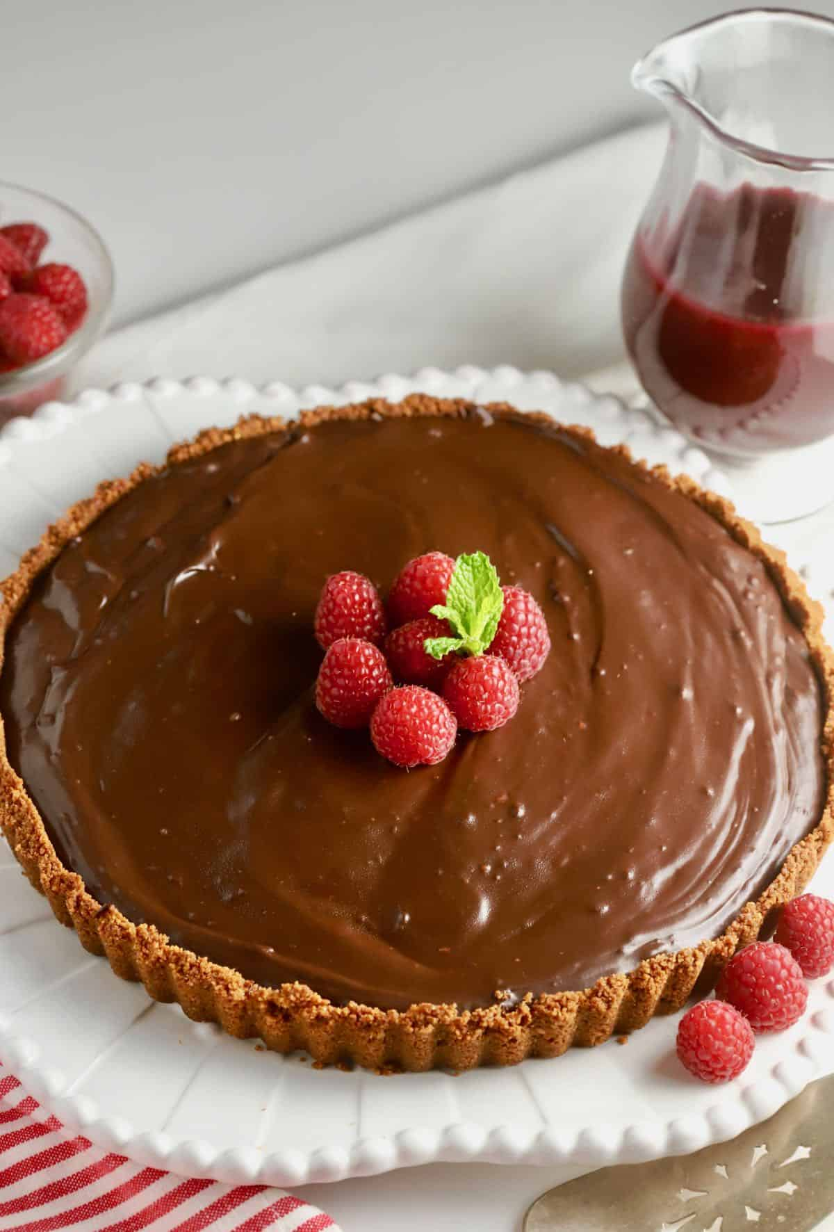 A chocolate ganache tart on a serving platter garnished with raspberries.