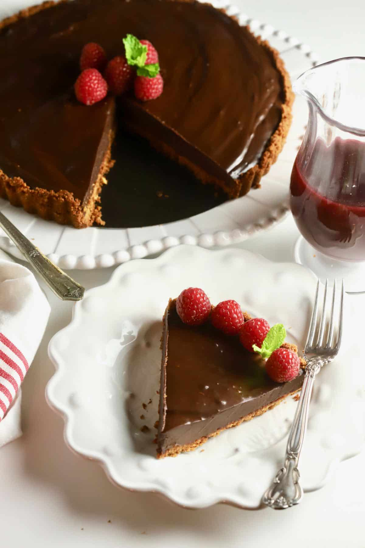 A chocolate ganache tart with a slice cut out and on a white plate.