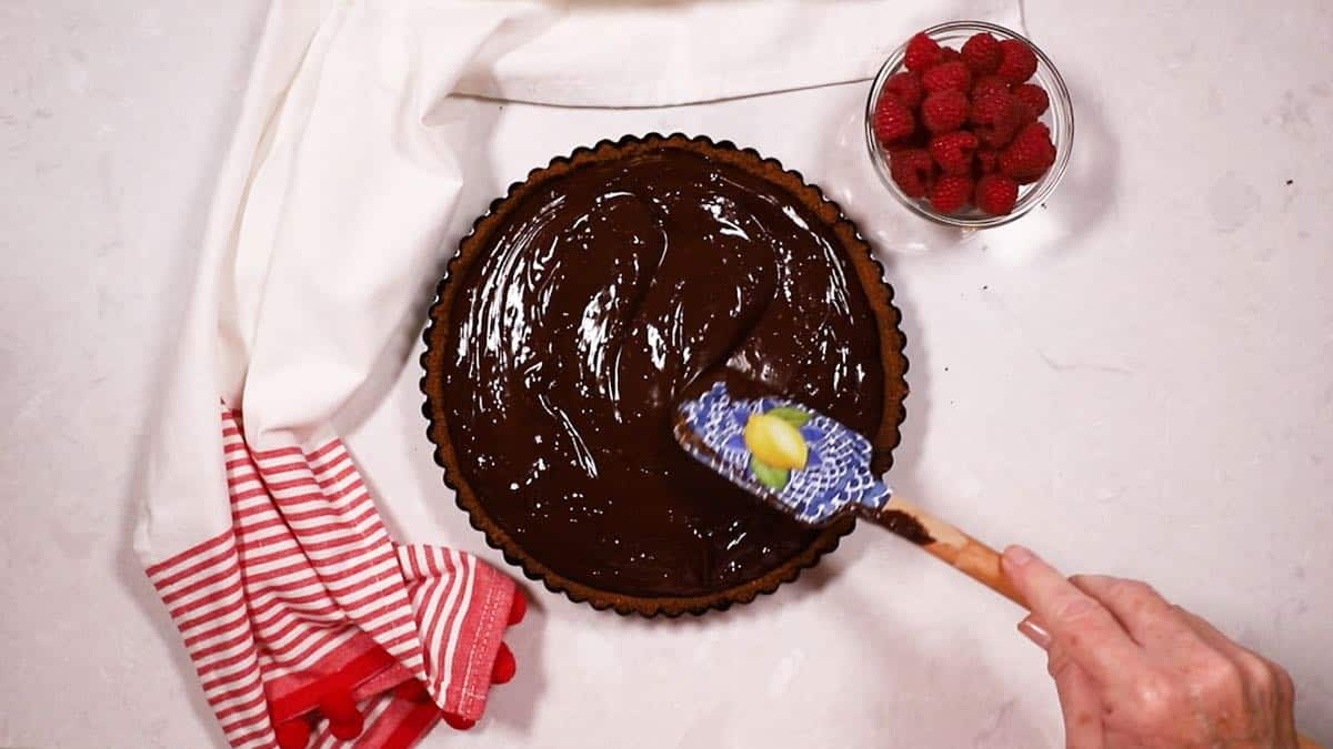 Using a rubber spatula to smooth our ganache filling in a tart crust.