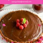 Pinterest pin, showing a chocolate tart topped with raspberries.