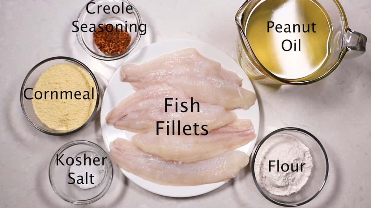 Ingredients for fried fish including fish fillets, and cornmeal.