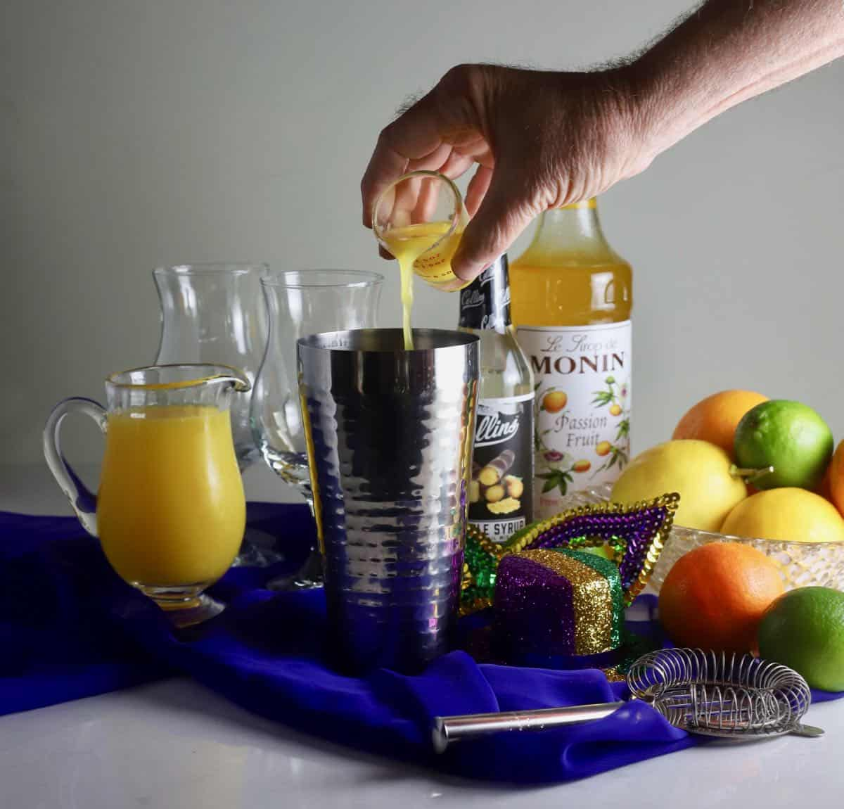 Adding a jigger of passion fruit juice to a metal cocktail shaker.