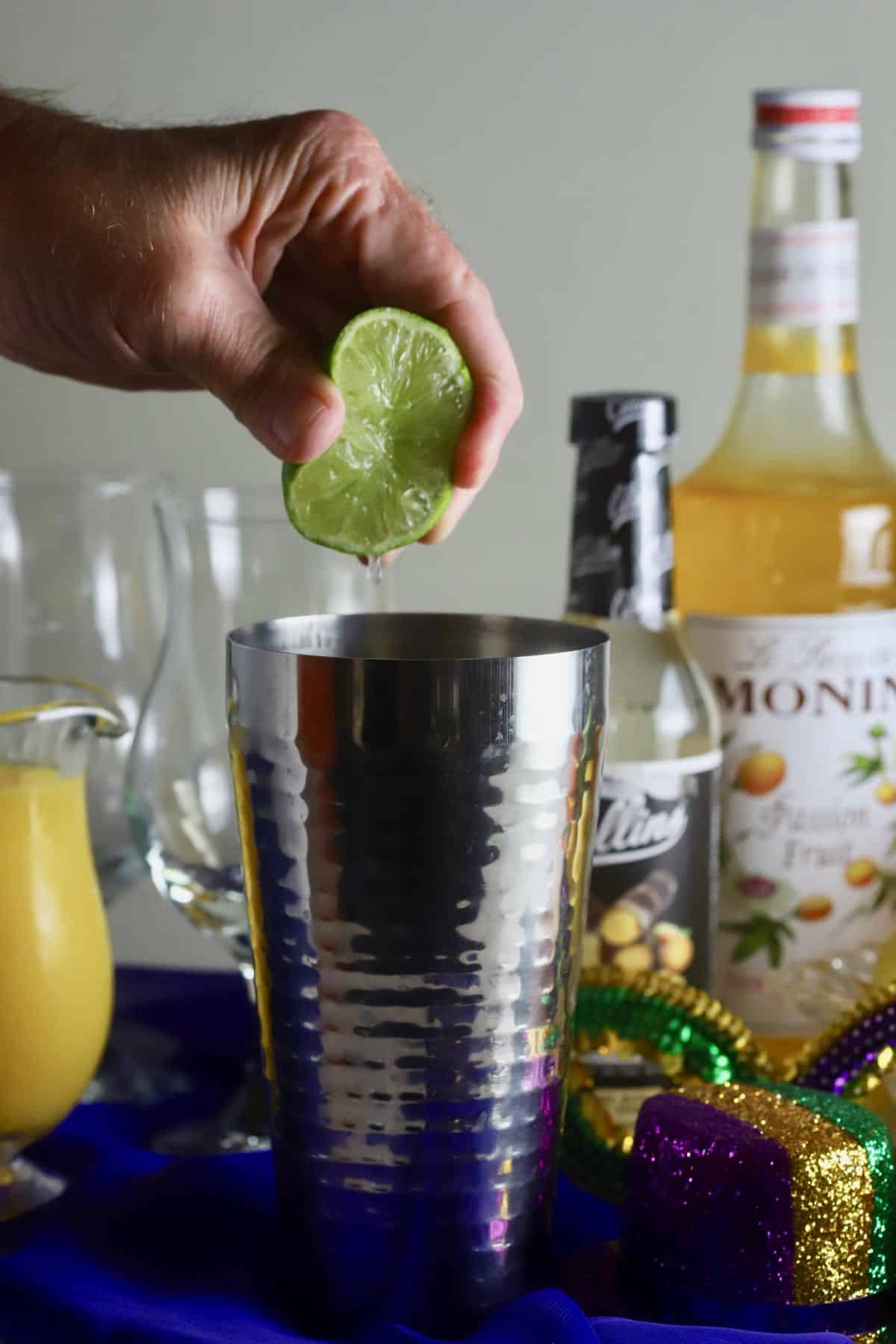 Adding lime juice to a cocktail shaker.