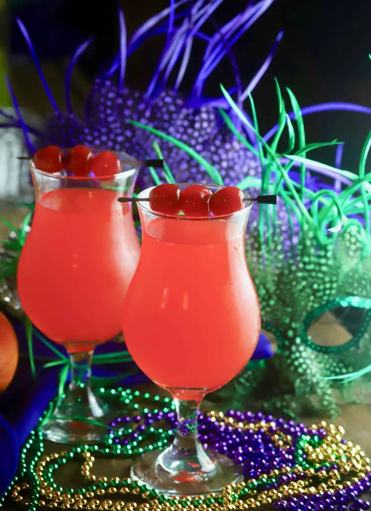 Two Hurricane cocktails on a table with Mardi Gras beads and masks.