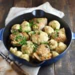 Chicken and cauliflower in a blue cast iron skillet.