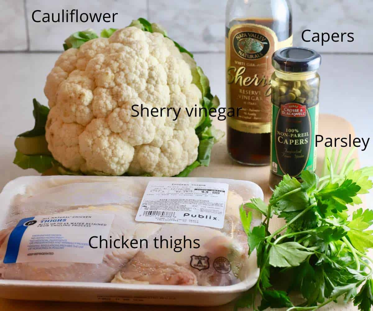 A head of cauliflower, chicken thighs, sherry vinegar and capers on a kitchen counter.