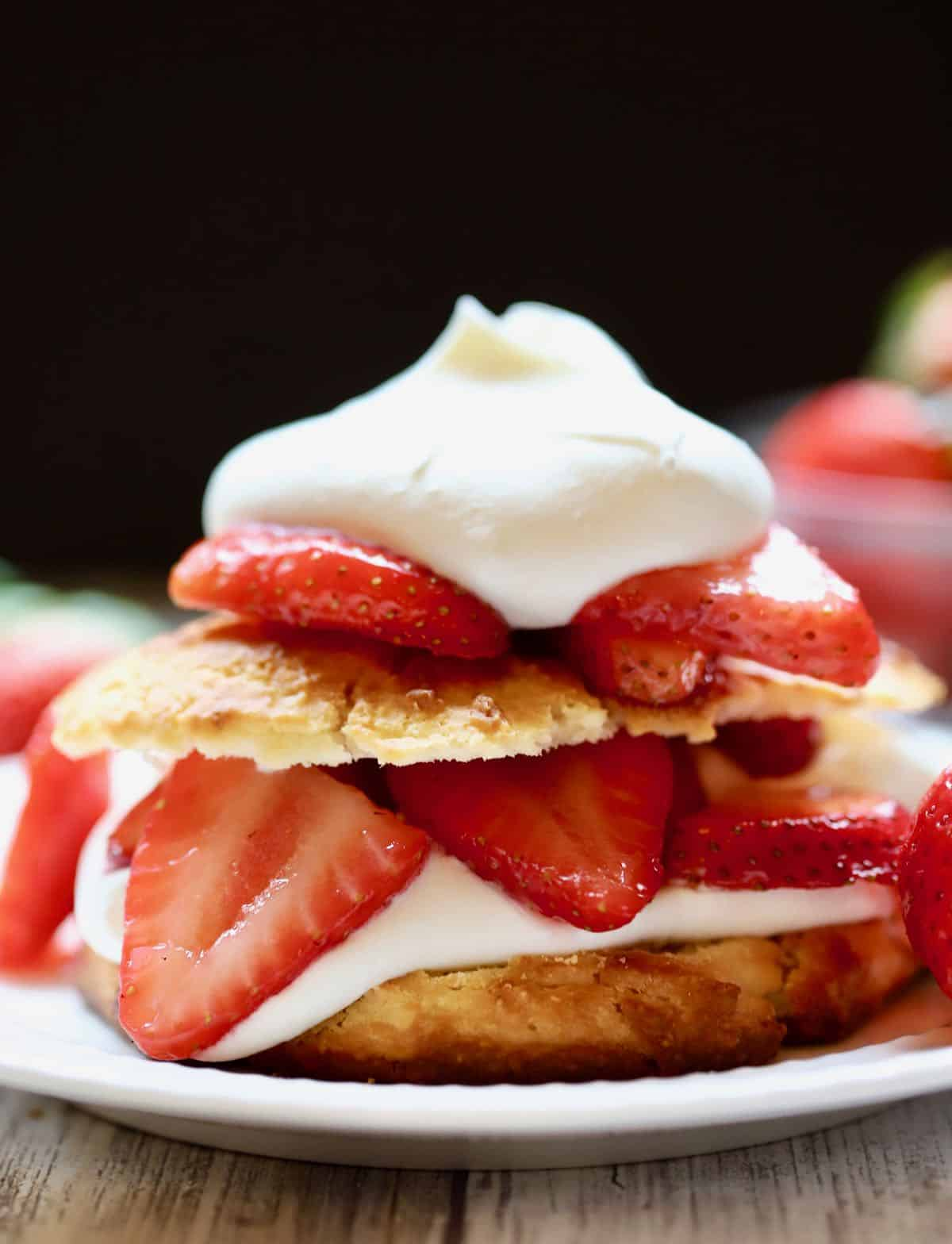 Southern strawberry shortcake on a plate with fresh strawberries.