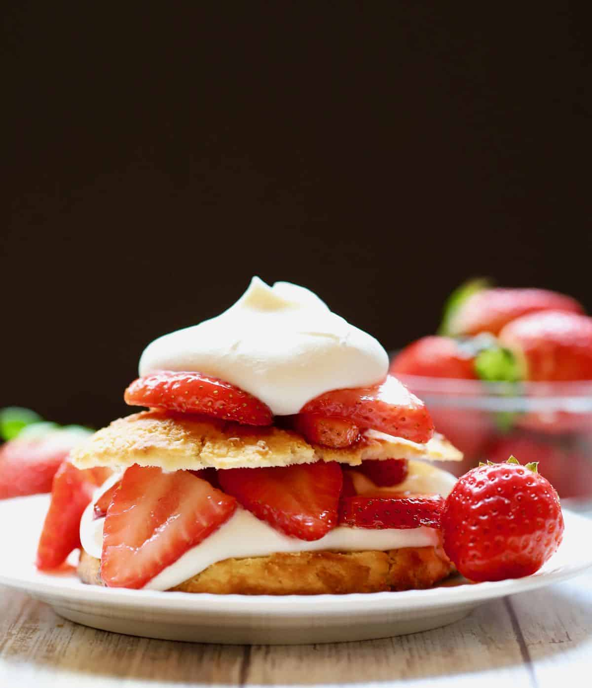 Strawberry shortcake with sliced strawberries on a plate.