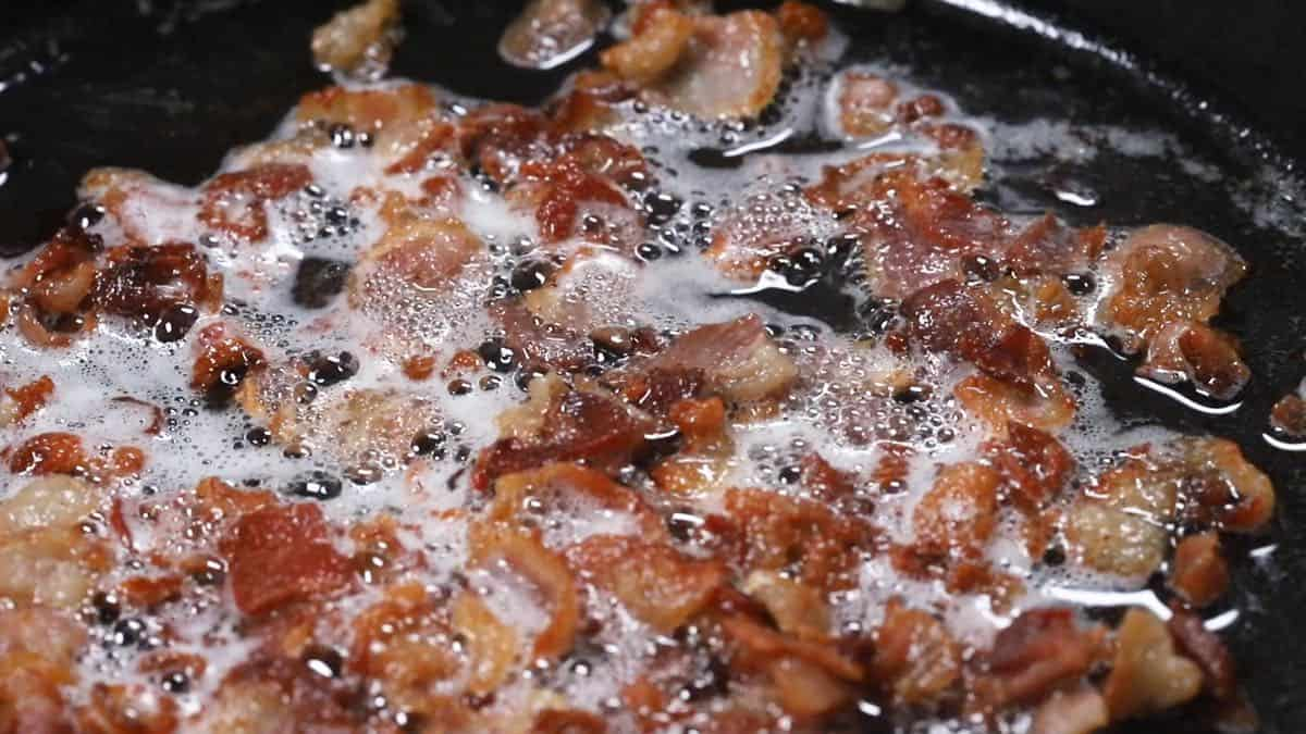 Bacon pieces cooking in a skillet.