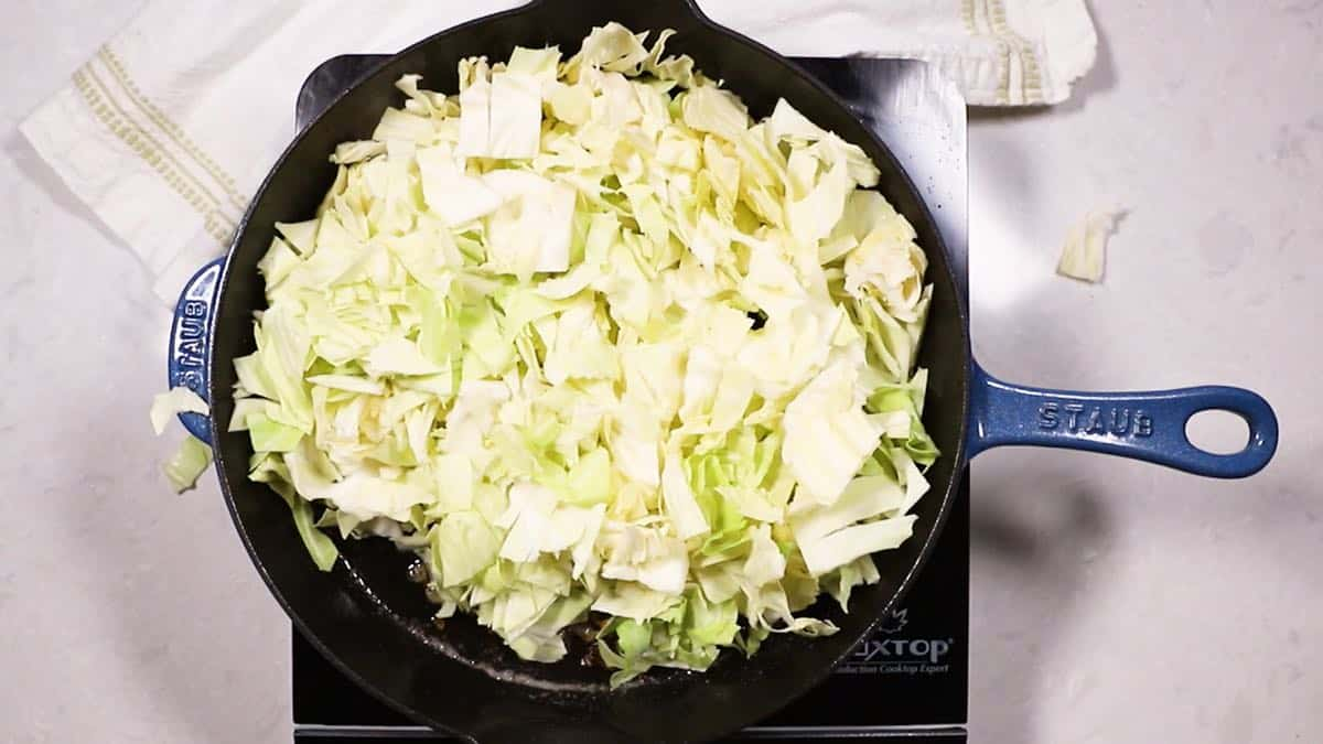 Cooking cabbage in a cast-iron skillet.