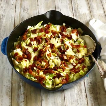 A cast iron skillet with Southern fried cabbage topped with bacon.