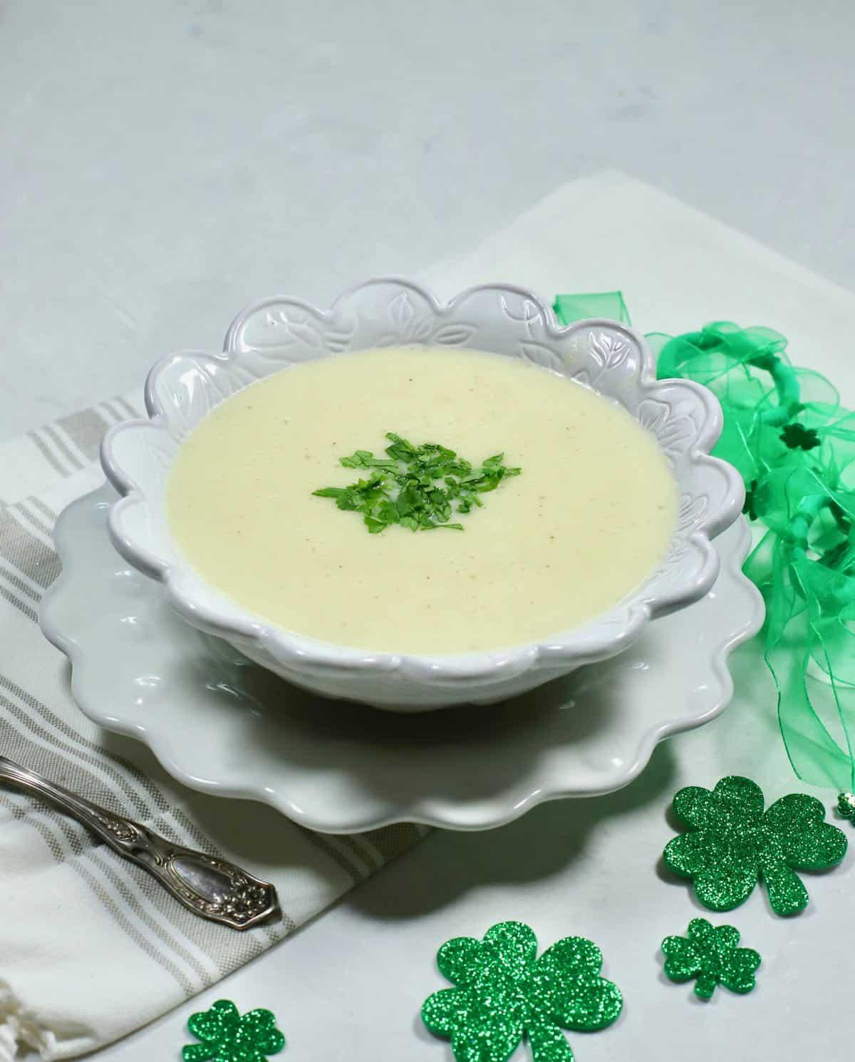 A white bowl full of potato soup with green shamrocks.