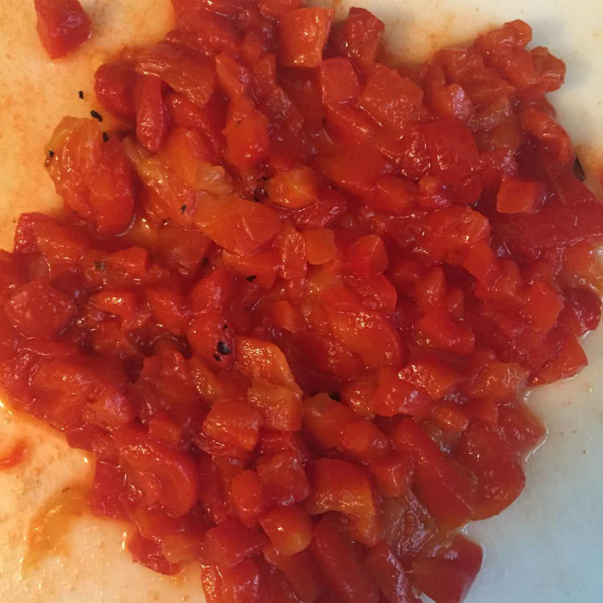 Minced roasted red bell pepper on a cutting board.