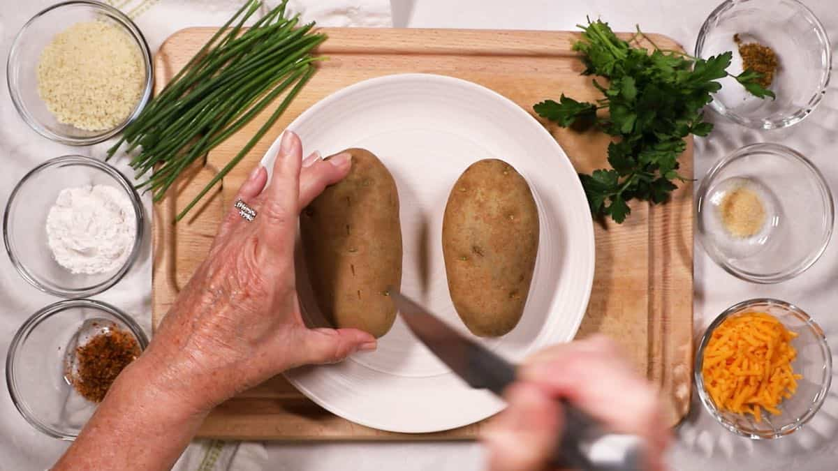 Using a knife to prick holes in a baking potato.
