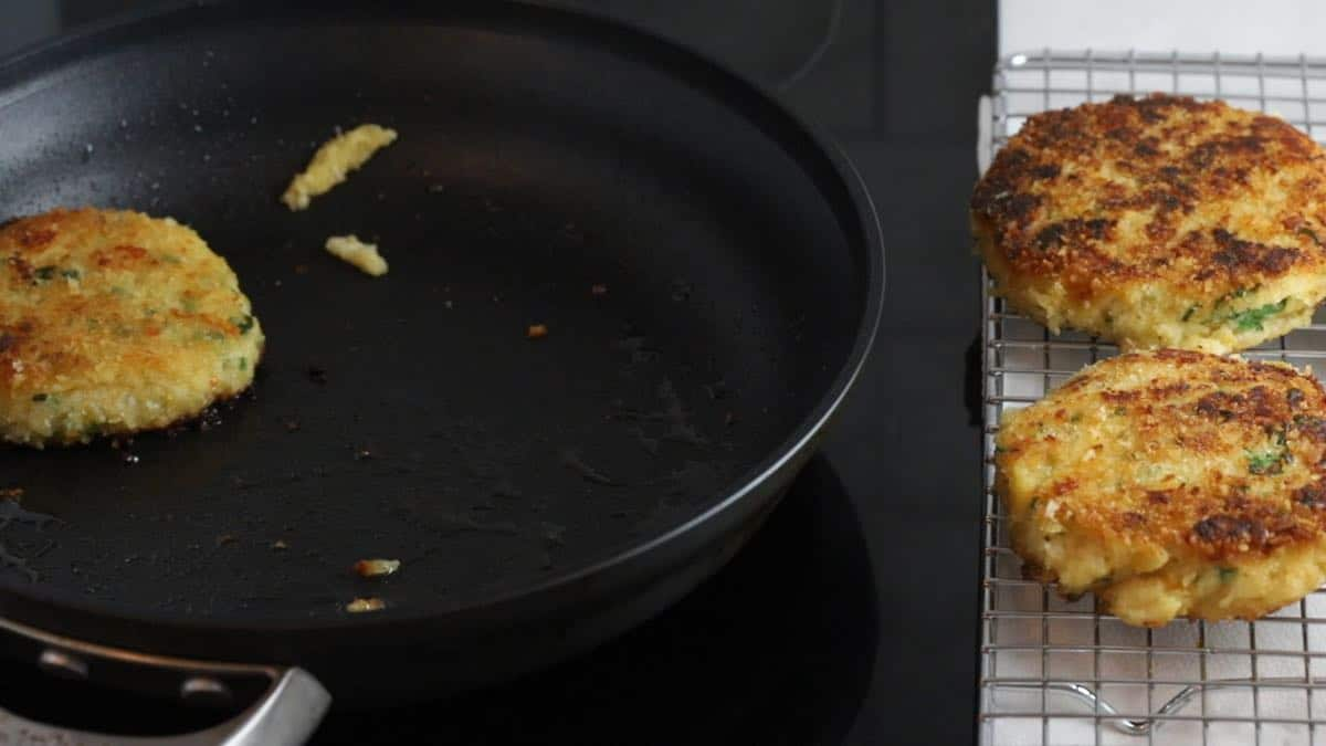 Removing potato fritters from a skillet and placing them on a wire rack.