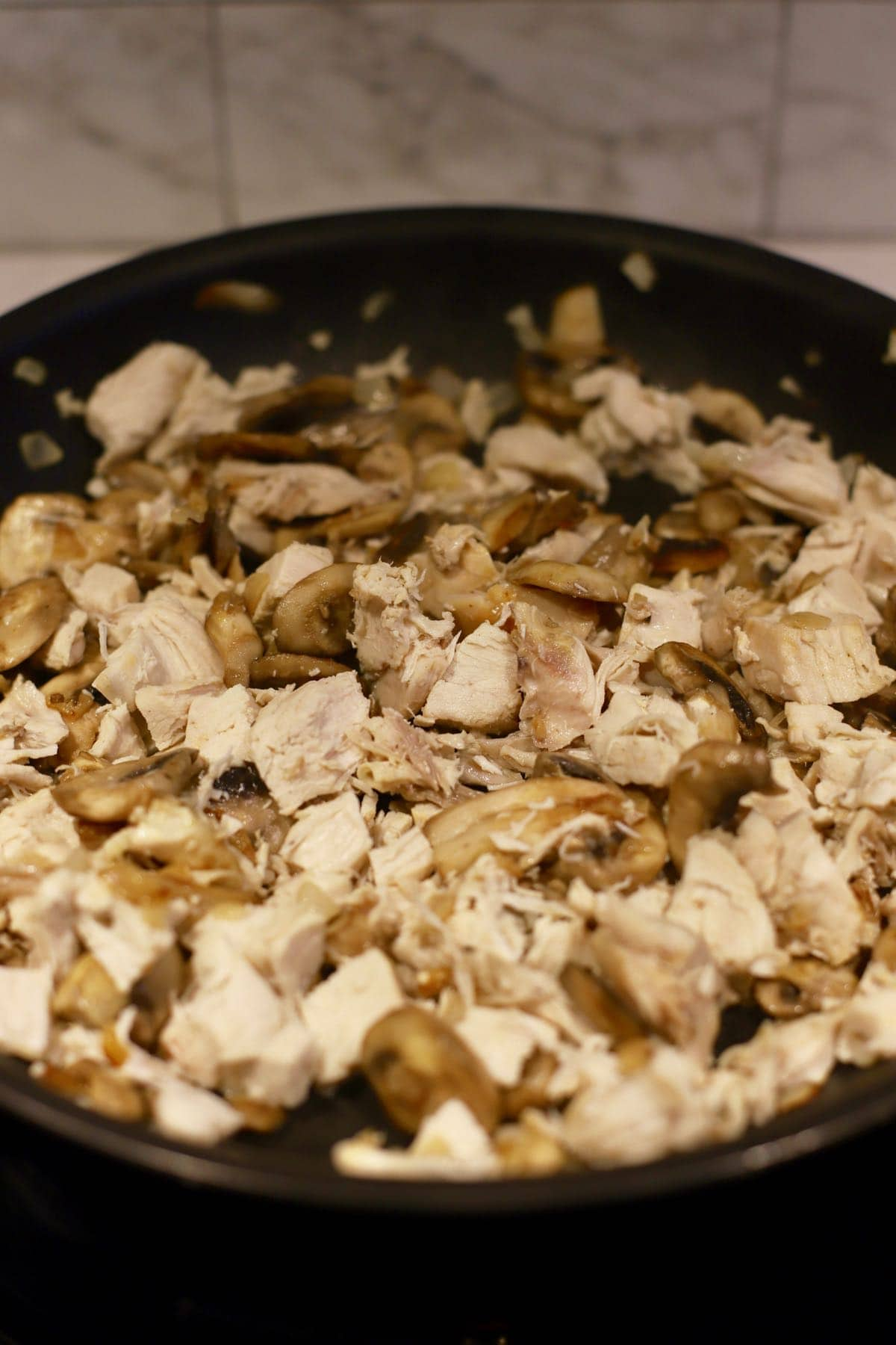 Pieces of cooked chicken and sliced mushrooms in a skillet.