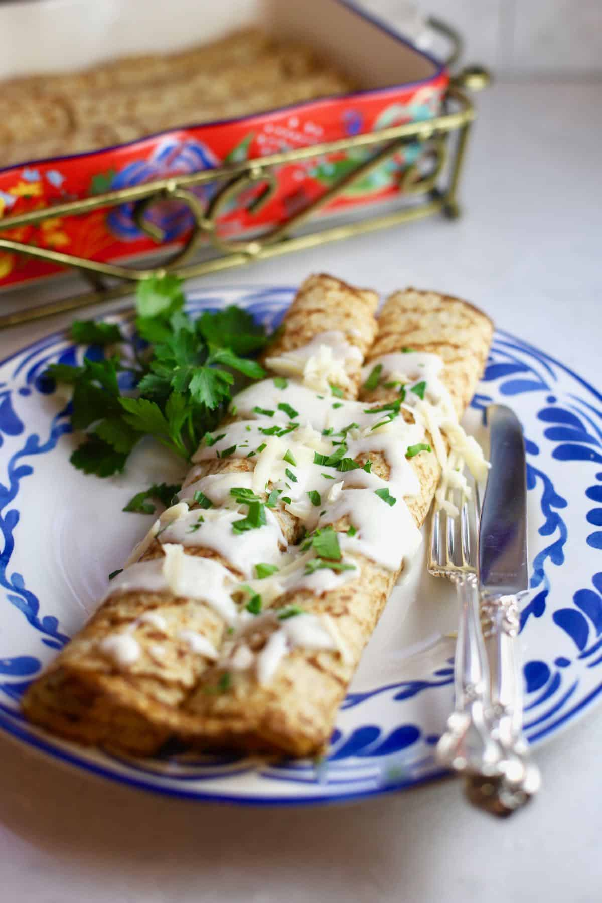 Chicken crepes on a blue and white dish with a knife and fork.