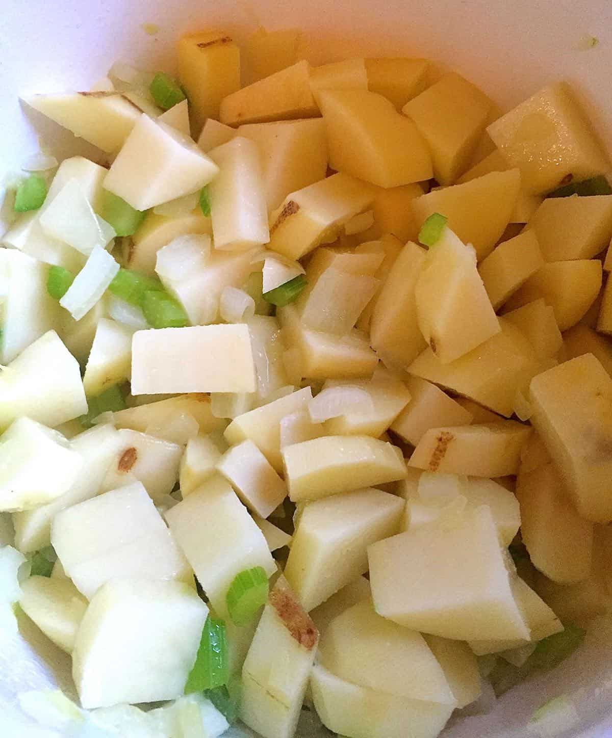 A saucepan with cut-up potatoes and celery.