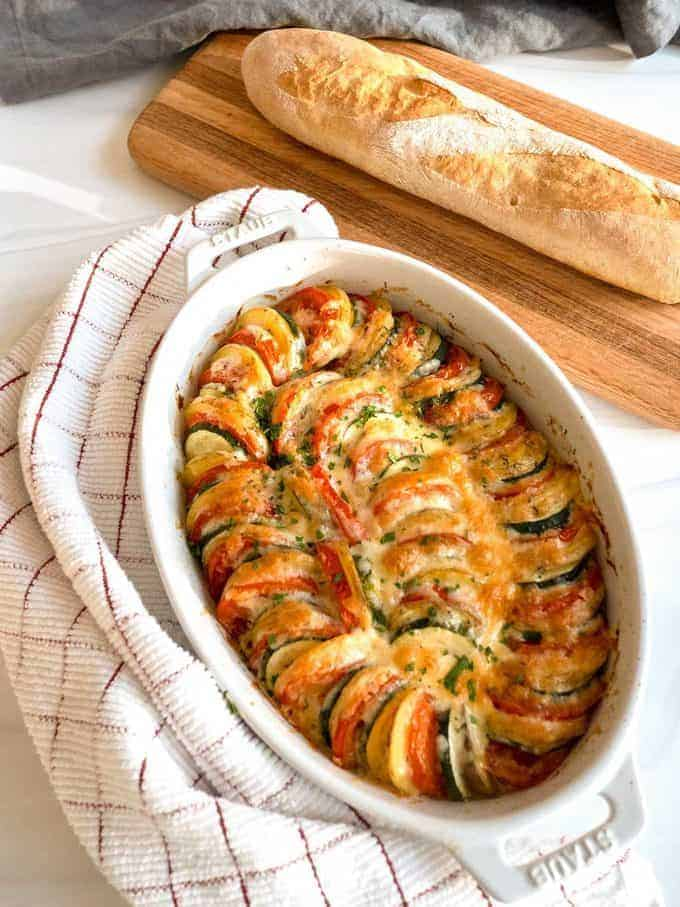 Vegetable Tian in a white baking dish with a loaf of French bread.