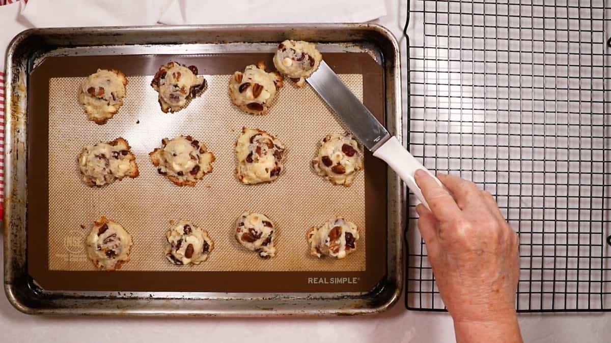 Using a spatula to remove cooled cookies from a baking sheet.