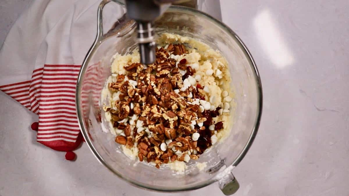 Cookie dough in a mixing bowl with pecans and cranberries.