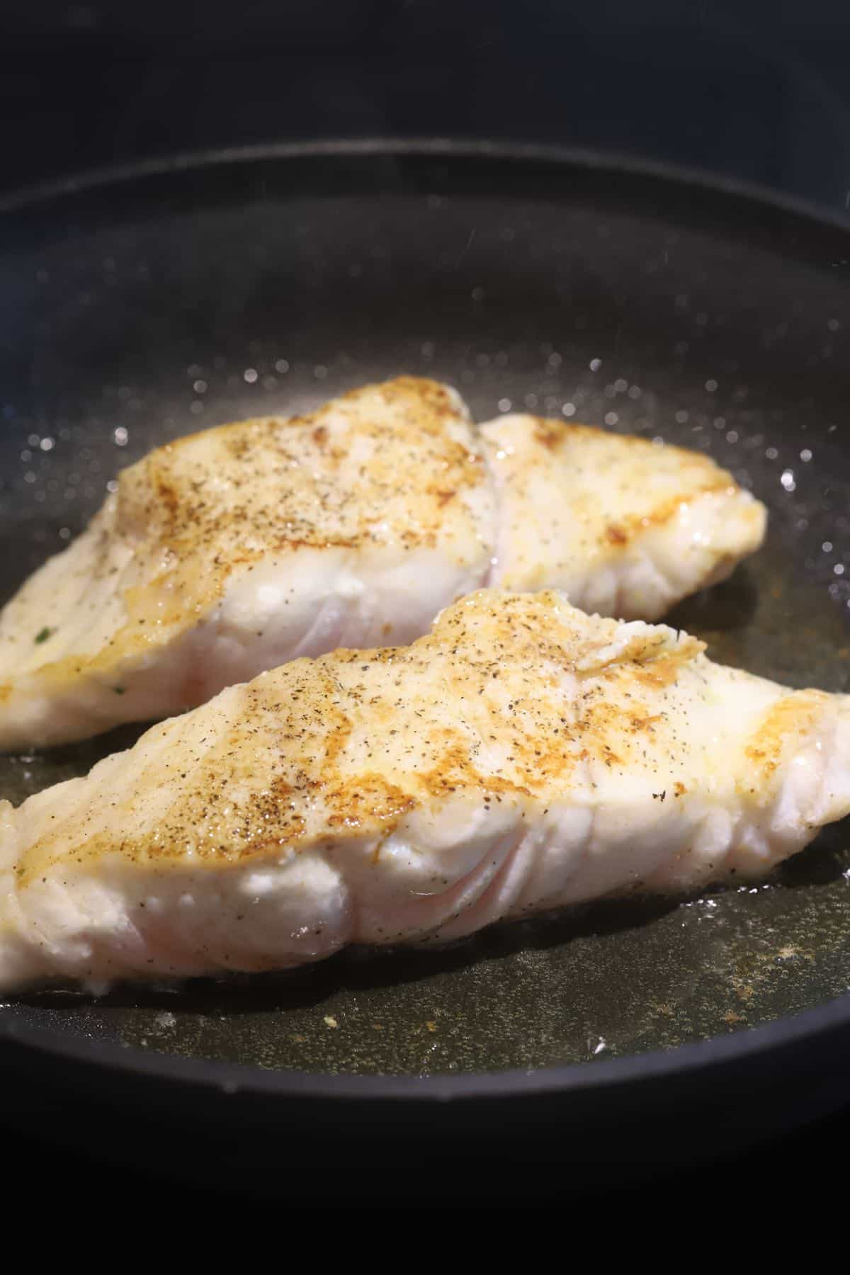 Two grouper fillets cooking in a skillet.