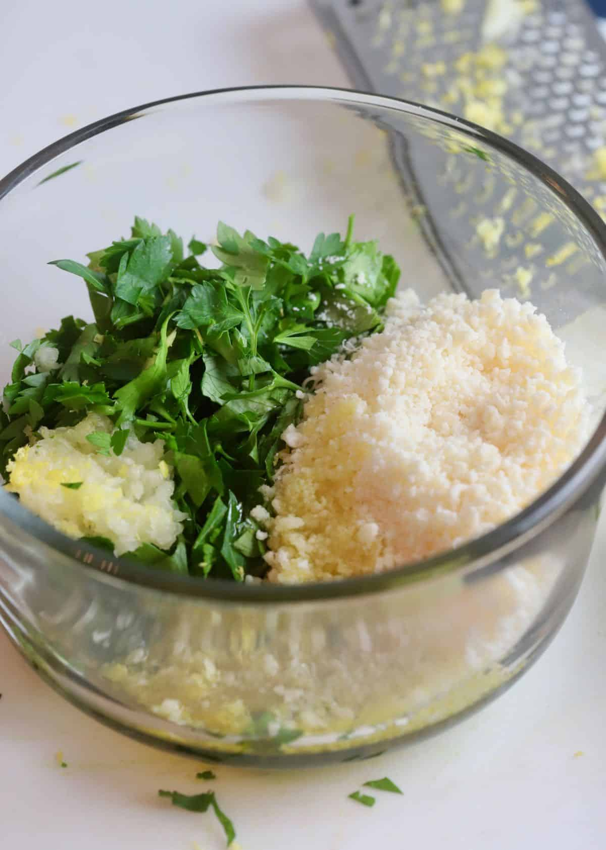 Gremolata ingredients in a bowl including lemon zest and parsley.