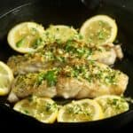 Cooked fish fillets topped with gremolata and garnished with lemon slices.