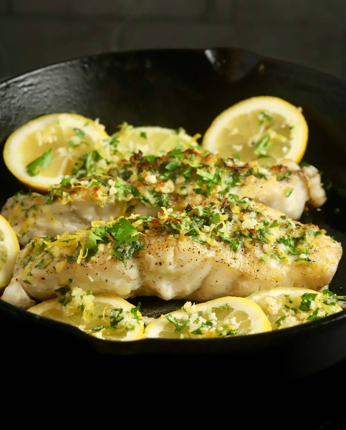 Two grouper fillets topped with gremolata in a cast-iron skillet with lemon slices.