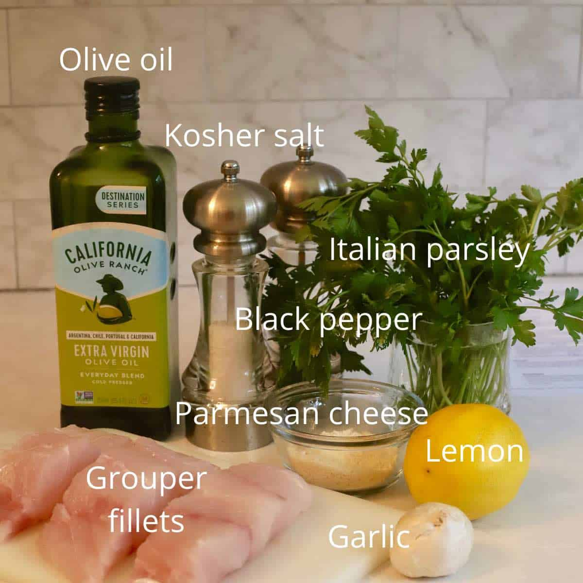 Ingredients like fish fillets, lemon and parsley on a cutting board.