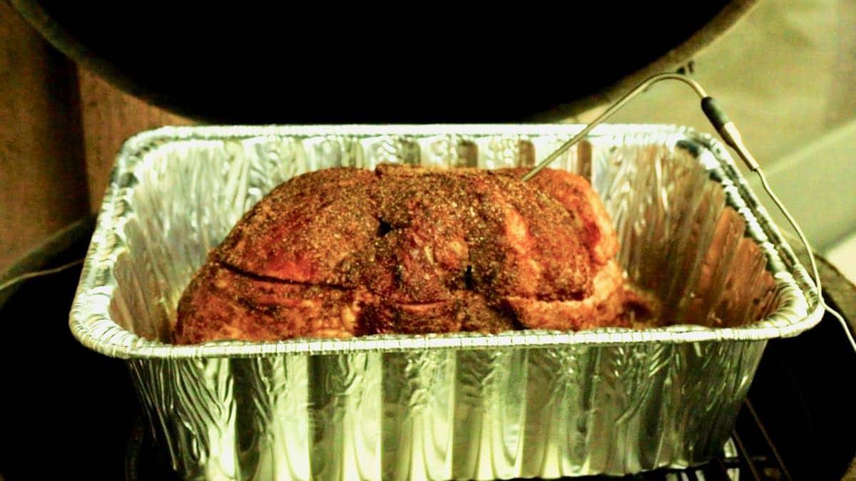 Temperature probe in a ham on a grill.