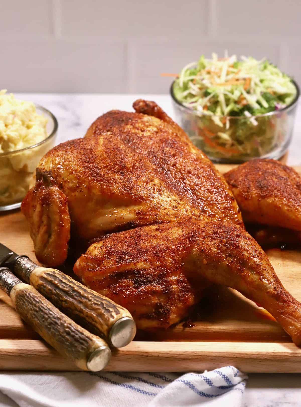A smoked whole chicken on a cutting board.