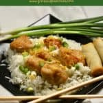 Pinterest pin showing lemon curd chicken served over rice on a black plate.