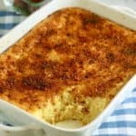An oven-baked Cheese Grits Casserole in a white baking dish.