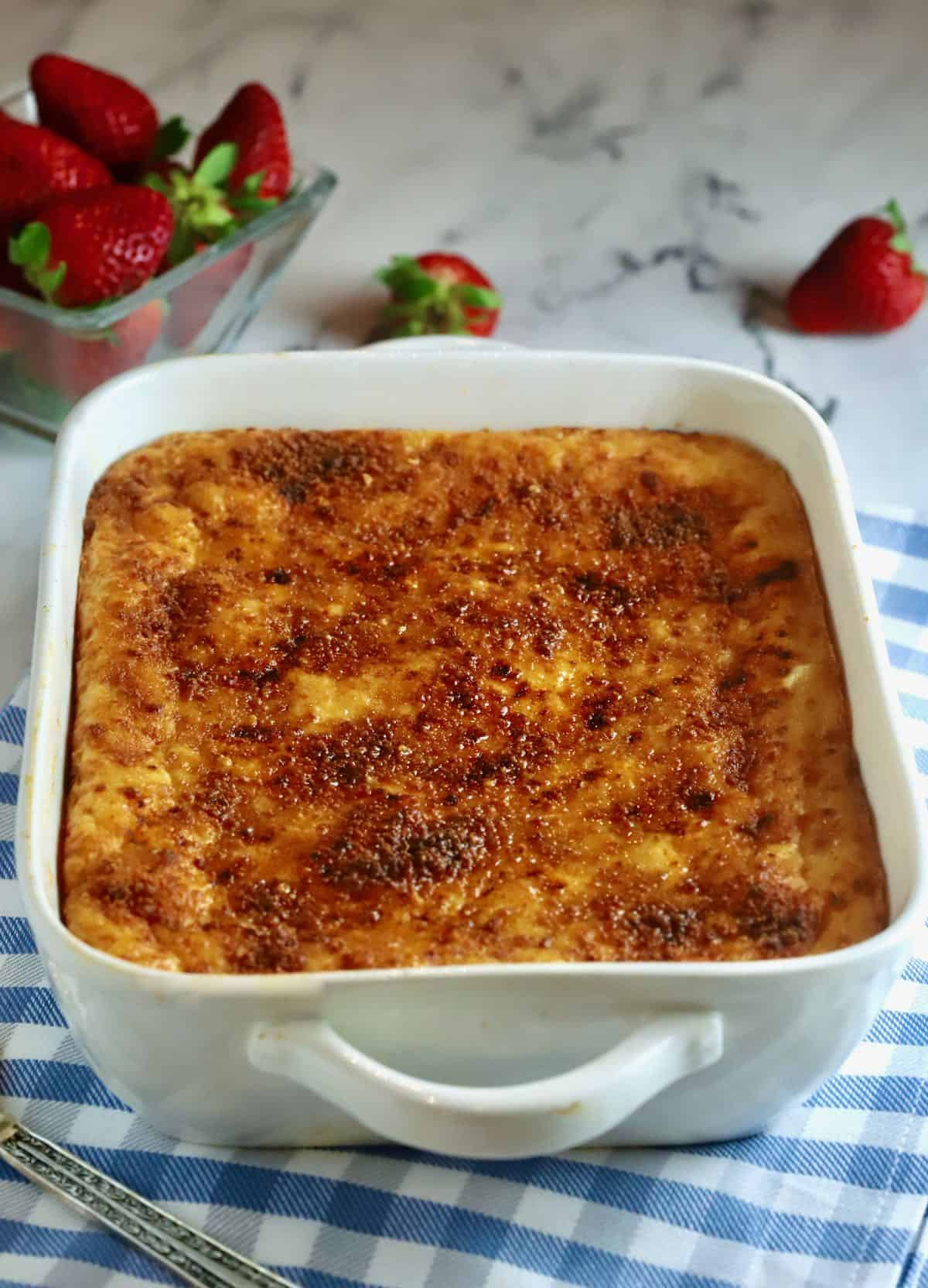 A baked cheese grits casserole on a blue and white kitchen towel.