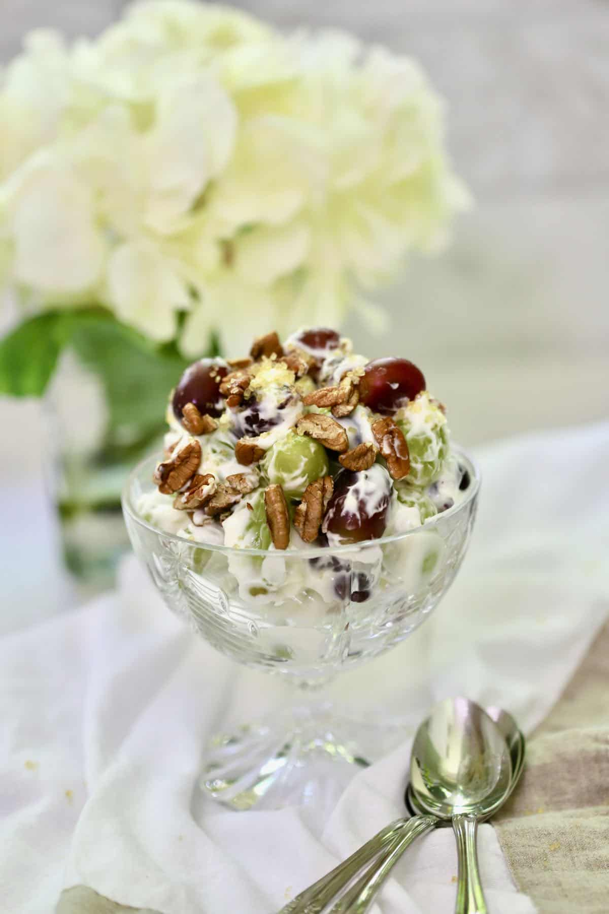 Grape salad topped with pecans in a crystal dessert dish.