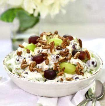 Grape salad topped with pecans and brown sugar in a white bowl.
