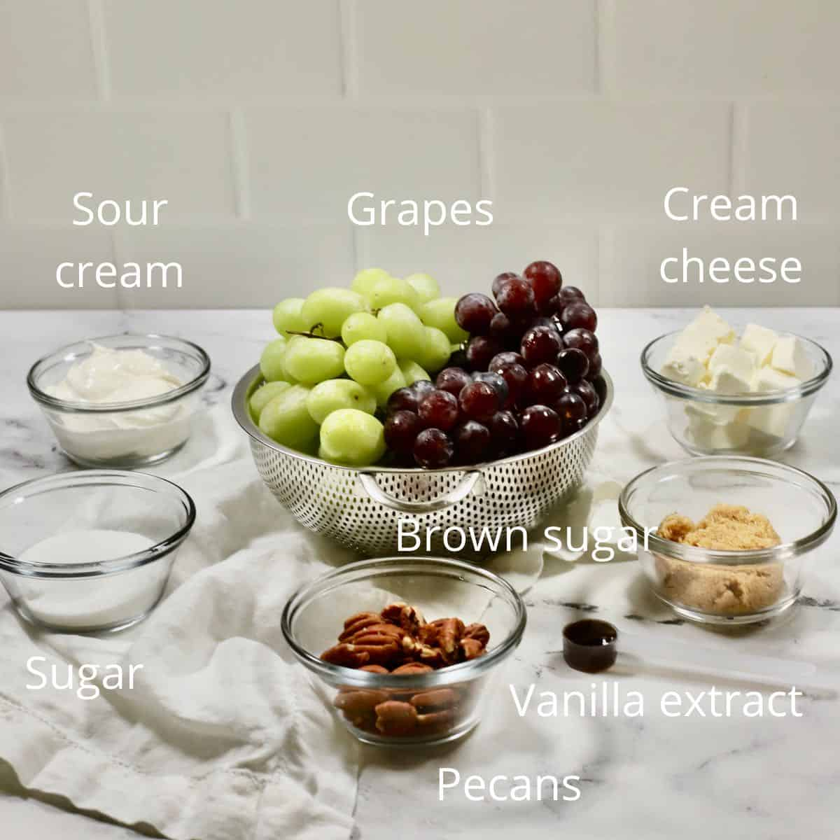 Grapes in a colander, and bowls of sugar, sour cream, and cream cheese.