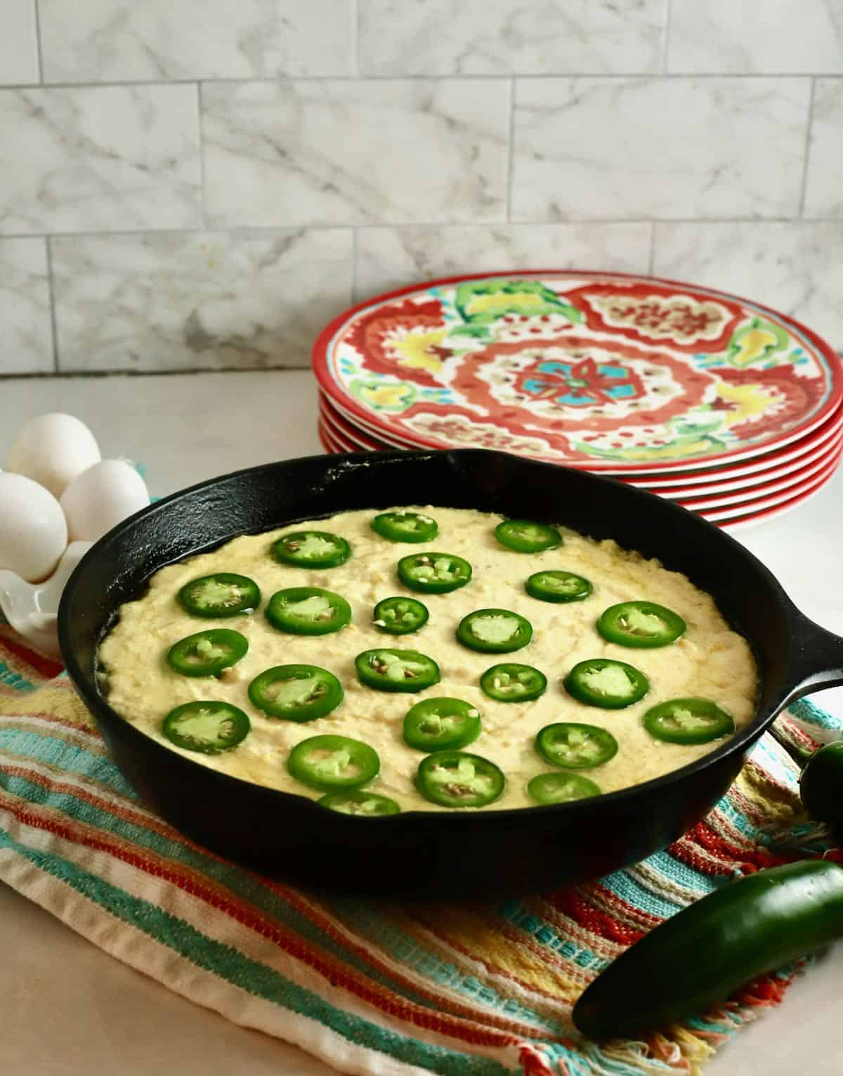 Cornbread batter topped with jalapeno slicess in a cast-iron skillet, ready for the oven.