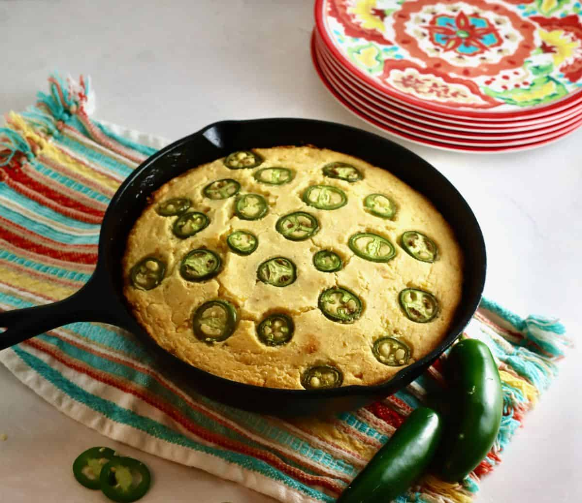Jalapeno cornbread in a cast iron skillet on a colorful dish towel.