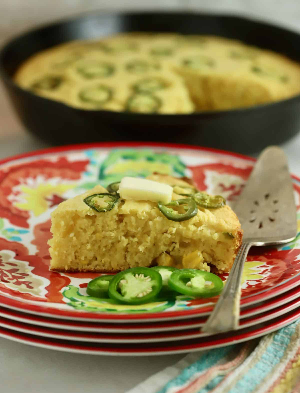 A slice of jalapeno cornbread on a colorful Mexican plate.